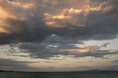 在多云天空的看法在海表面上在晚上 在日落以后的地平线与太阳和云彩前光芒  天气,季节 库存图片