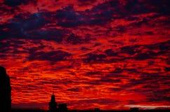 在多云天空的红色血淋淋的日落在村庄上 美好的乡下横向 免版税库存图片