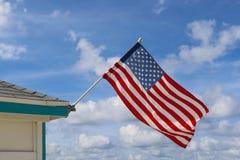 在多云天空的美国旗子 免版税库存图片