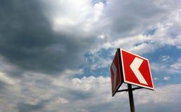 在多云天空背景的红色和白色警告箭头 库存图片