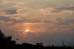 在多云天空,有点与剪影城市scape的黑暗的太阳 图库摄影