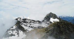 在多云岩石多雪的山的向前空中顶视图在与云彩的晴天 意大利阿尔卑斯山在夏天与 股票录像