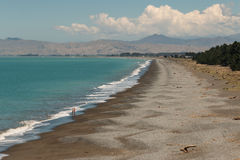 在多云海湾的有卵石花纹的海滩 免版税库存照片