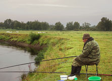 在多云的河的河岸的渔夫渔,有雾的mornin 免版税库存图片