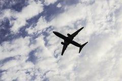在多云背景的飞机 免版税图库摄影