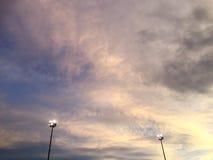 在多云蓝天的两盏聚光灯 免版税库存图片
