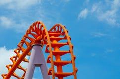 在多云蓝天背景在关闭的橙色过山车轨道隔绝的弯曲  库存图片