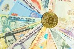 在多国家的钞票票据背景, bitcoin概念,美元,泰铢, ringit,比索的Bitcoin堆 库存照片