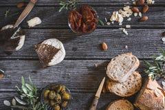 在多士上添面包用山羊乳干酪、干蕃茄、绿橄榄和杏仁夏天鸡尾酒的 库存照片