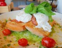 在多士的鸡蛋本尼迪克特用烟肉、火箭沙拉、鲕梨调味汁和蕃茄 库存照片