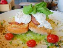 在多士的鸡蛋本尼迪克特用烟肉、火箭沙拉、鲕梨调味汁和蕃茄 免版税图库摄影