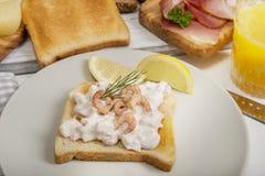 在多士面包、火腿和橙汁的虾沙拉 图库摄影
