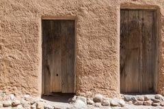 在多孔黏土墙壁上的老门 免版税图库摄影
