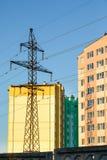 在多层的居民住房附近的输电线定向塔 库存图片