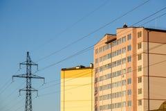 在多层的居民住房附近的输电线定向塔 免版税库存照片