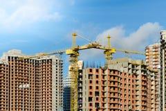 在多层的砖房子工地工作的两台黄色建筑用起重机反对天空蔚蓝的 免版税库存照片