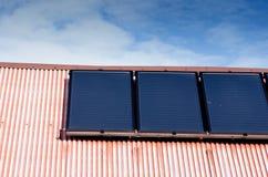在多山墙郊区房子屋顶的可更新的干净的绿色节能高效率的光致电压的太阳电池板在蓝天芒什省 库存照片