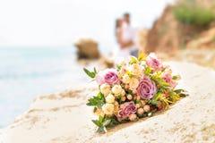 在多岩石的海滩的婚礼花束 库存图片