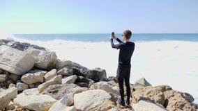 在多岩石的海滩藏品电话的年轻适合的白种人人身分和谈话,当拍击中岩石时的海和波浪的照片 影视素材