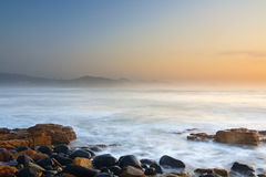 在多岩石的海滩,东部伦敦,南非的日出 库存图片