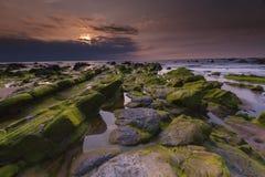 在多岩石的海滩III的日落 库存图片
