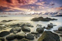在多岩石的海滩的日出在terengganu,马来西亚 图象采取与长的曝光,习惯白色平衡 免版税库存照片