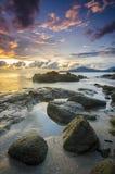 在多岩石的海滩的日出在terengganu,马来西亚 图象采取与长的曝光,习惯白色平衡 库存照片