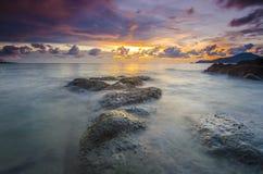 在多岩石的海滩的日出在terengganu,马来西亚 图象采取与长的曝光,习惯白色平衡 免版税库存图片