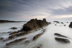 在多岩石的海滩的日出 库存照片