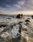 在多岩石的海滩的日出 免版税库存照片