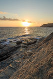 在多岩石的海滩的日出 库存图片