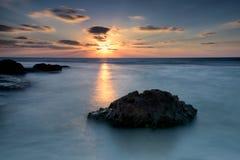 在多岩石的海滩的日落射线 免版税库存图片