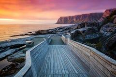 在多岩石的海滩的木路 图库摄影