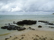 在多岩石的海滩的波浪 免版税图库摄影