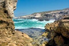 在多岩石的海滩的令人敬畏的看法在两个岩石之间 免版税图库摄影