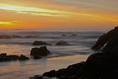在多岩石的海滩,南非的日落 免版税库存图片