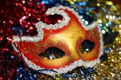 在多彩多姿的圣诞节树闪亮金属片背景的明亮的红金面具  免版税库存图片