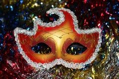 在多彩多姿的圣诞节树闪亮金属片背景的明亮的红金面具  免版税库存照片