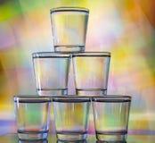 在多彩多姿的背景的一个塔堆积的六块玻璃 库存图片