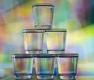 在多彩多姿的背景的一个塔堆积的六块玻璃 库存照片