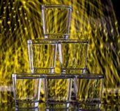 在多彩多姿的背景的一个塔堆积的六块玻璃 免版税库存照片