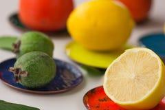 在多彩多姿的铜版的果子:柿子,柠檬 柠檬新鲜水果柿子Feijoa白色背景 库存照片