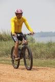 年轻在多灰尘的r的人佩带的车手衣服骑马登山车MBT 免版税库存照片