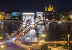 在多瑙河和圣斯蒂芬` s的铁锁式桥梁大教堂在晚上,布达佩斯,匈牙利 免版税图库摄影