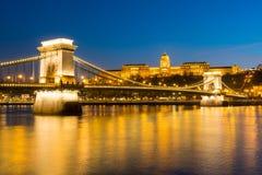 在多瑙河的铁锁式桥梁日落的在布达佩斯,匈牙利 图库摄影