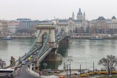 在多瑙河的铁锁式桥梁有汽车的,电车和马达在布达佩斯,匈牙利运送 美丽的景色在虫边 免版税库存图片