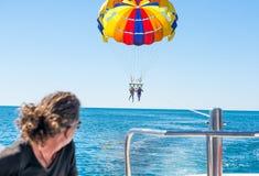 在多米尼加海滩的愉快的夫妇帆伞运动在夏天 在垂悬空中的降伞下的夫妇 免版税库存图片