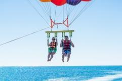在多米尼加海滩的愉快的夫妇帆伞运动在夏天 在垂悬空中的降伞下的夫妇 儿童有父亲的乐趣一起使用 热带的天堂 POS 图库摄影
