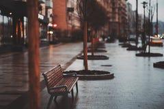 在多雨城市布局的长凳 免版税库存图片