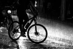 在多雨夜期间,骑自行车在交通 免版税库存图片